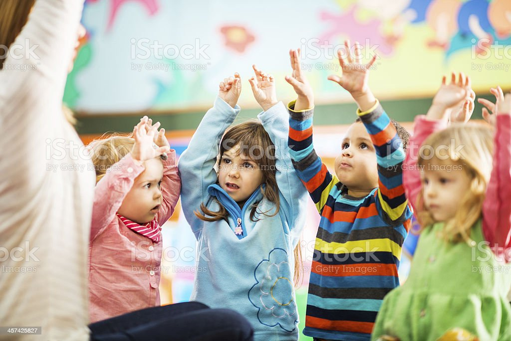 Kids playing with their teacher. stock photo