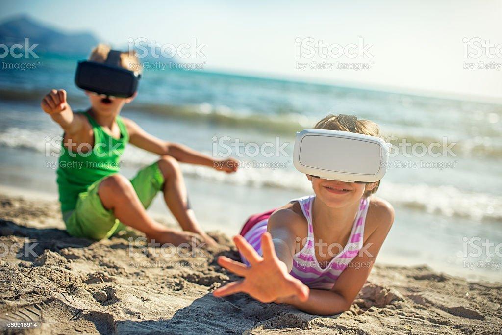Kids playing with virtual reality headset stock photo