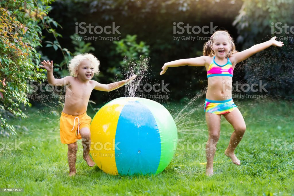 Kids playing with water ball toy sprinkler stock photo