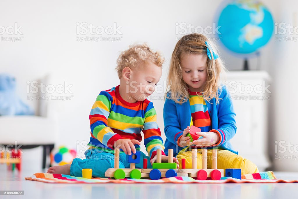 Kids playing with wooden toy train stock photo