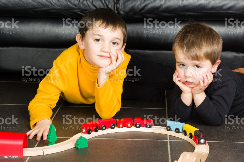 Kids (boys) playing with wooden trains stock photo