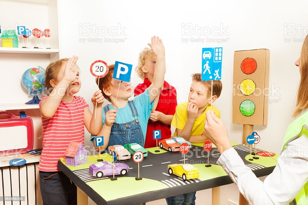 Kids raising their hands up at road safety lesson stock photo