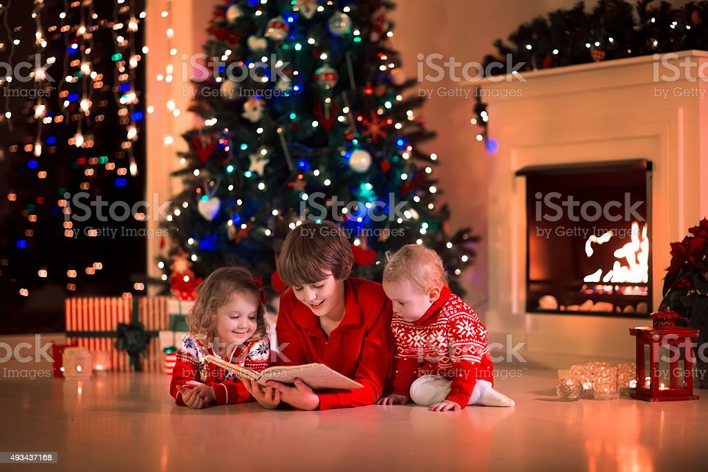 Kids reading a book on Christmas eve at fireplace stock photo