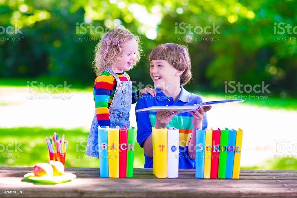 Kids reading in school yard stock photo