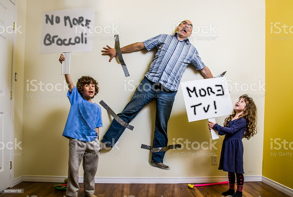 Kids rebellion led to strapping the father on wall stock photo