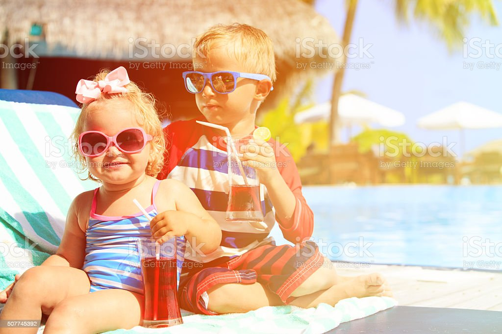 kids relax on tropical beach resort and drink juices stock photo