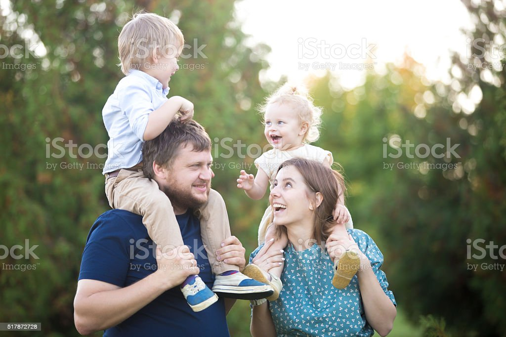 Kids riding on parents in park stock photo