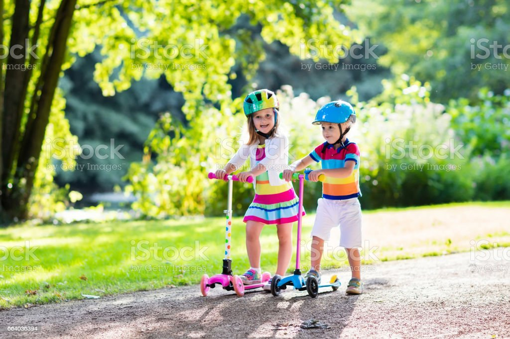 Kids riding scooter in summer park. stock photo