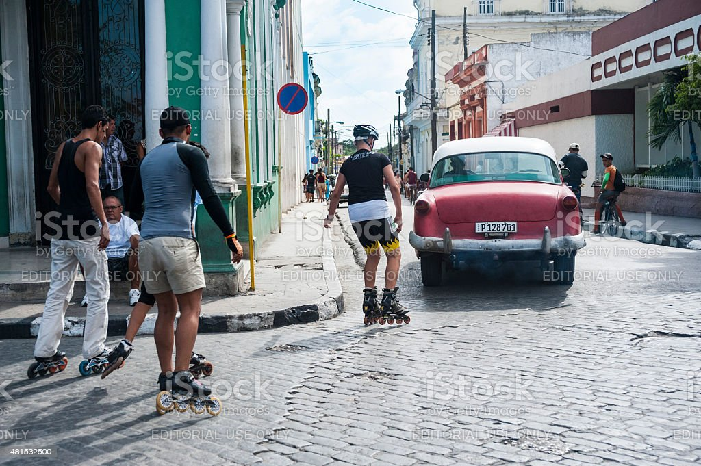 Kids rollerblade behind a vintage car in Cuba stock photo