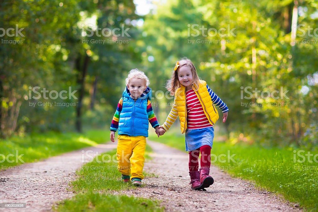 Kids running in autumn park stock photo