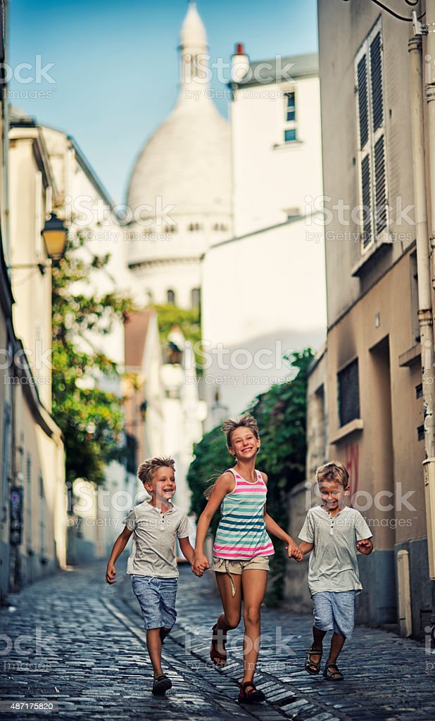 Three kids visiting Paris. They are holding hands and having fun in...