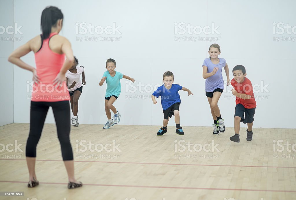 Kids running in gym class stock photo