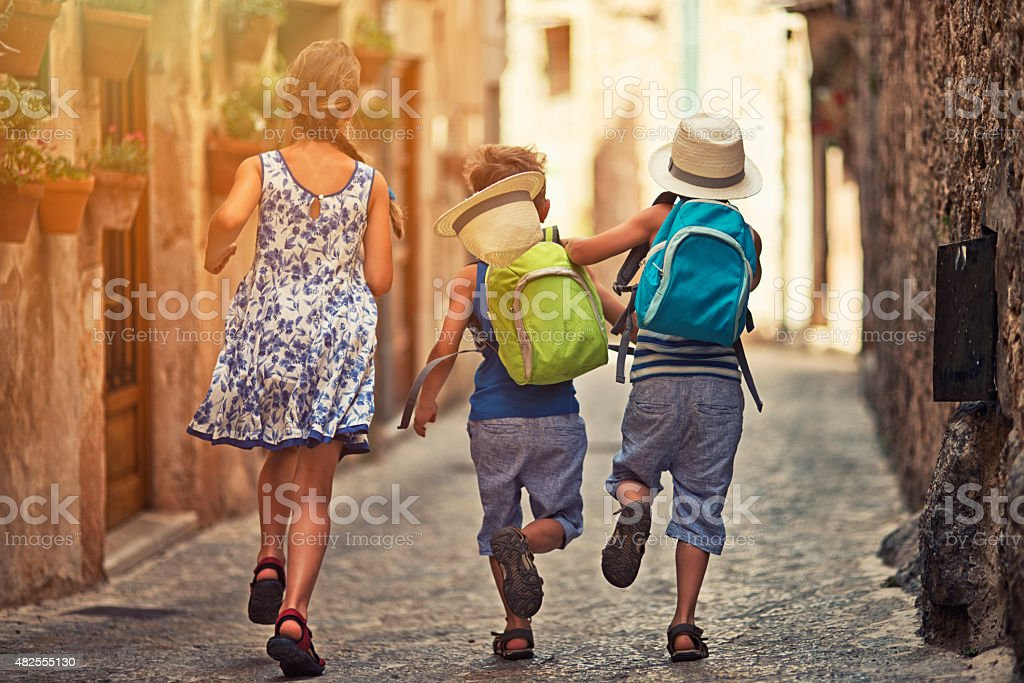 Kids running in mediterranean street. stock photo