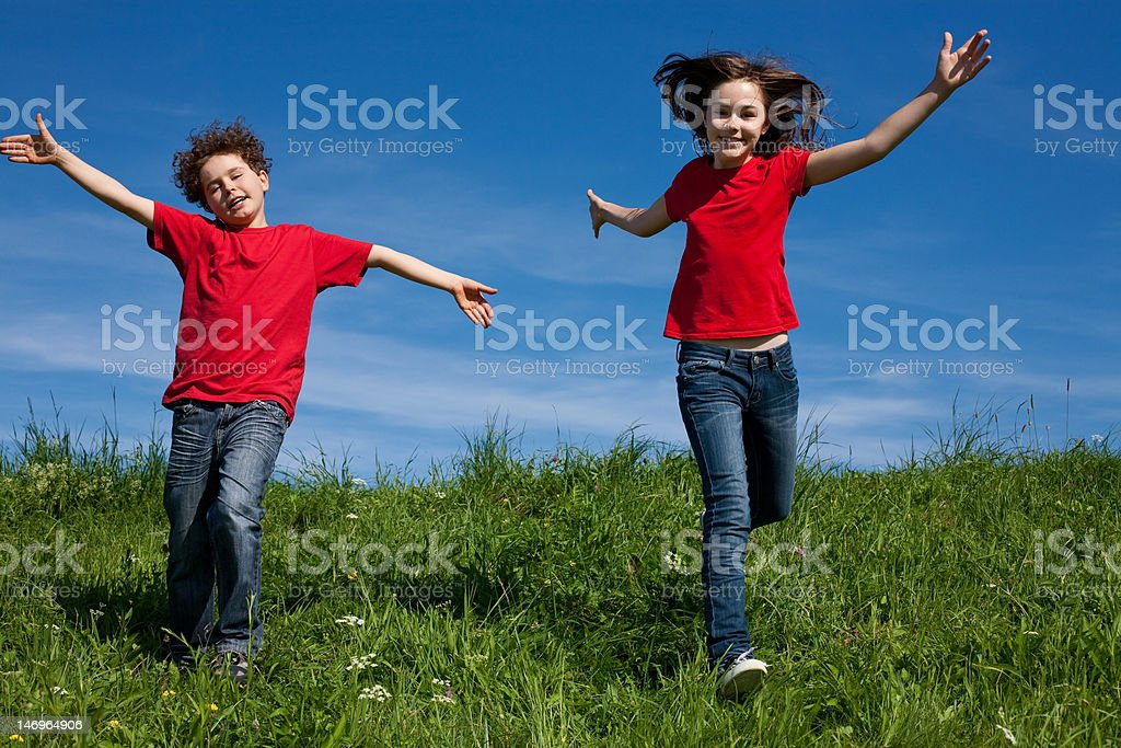 Kids running, jumping outdoor against blue sky royalty-free stock photo