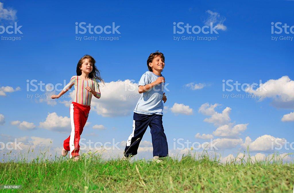 Kids running on meadow stock photo
