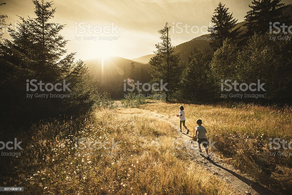 Kids running towards the sun stock photo