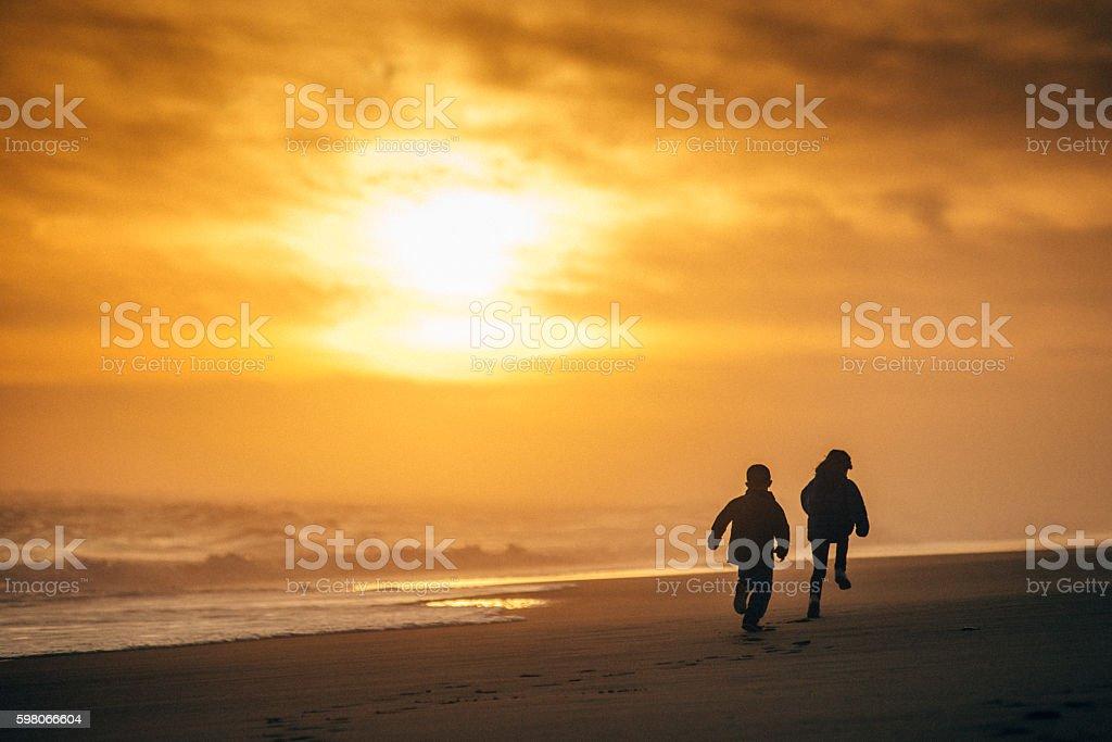 Kids running towards the sun stock photo