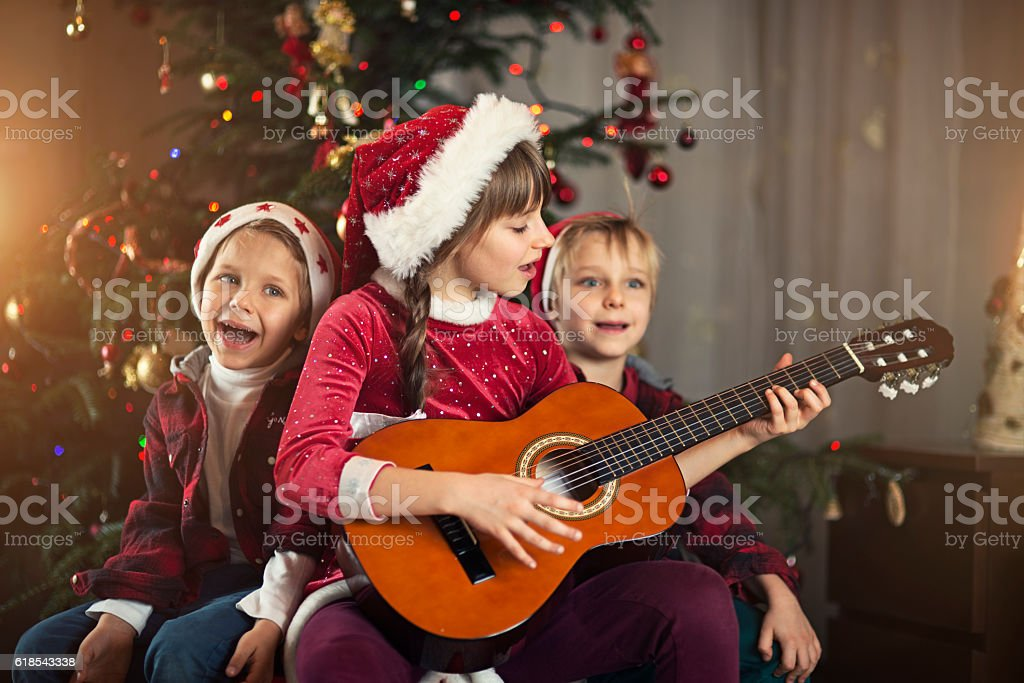 Kids singing carols near the christmas tree stock photo
