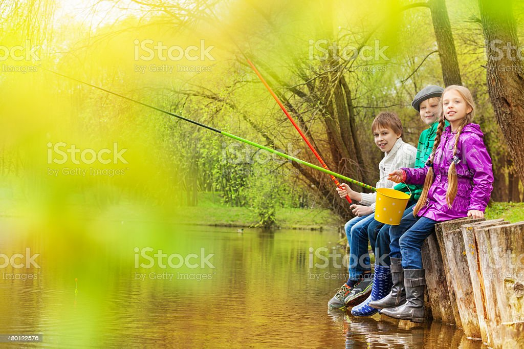 Kids sitting and fishing together near the pond stock photo