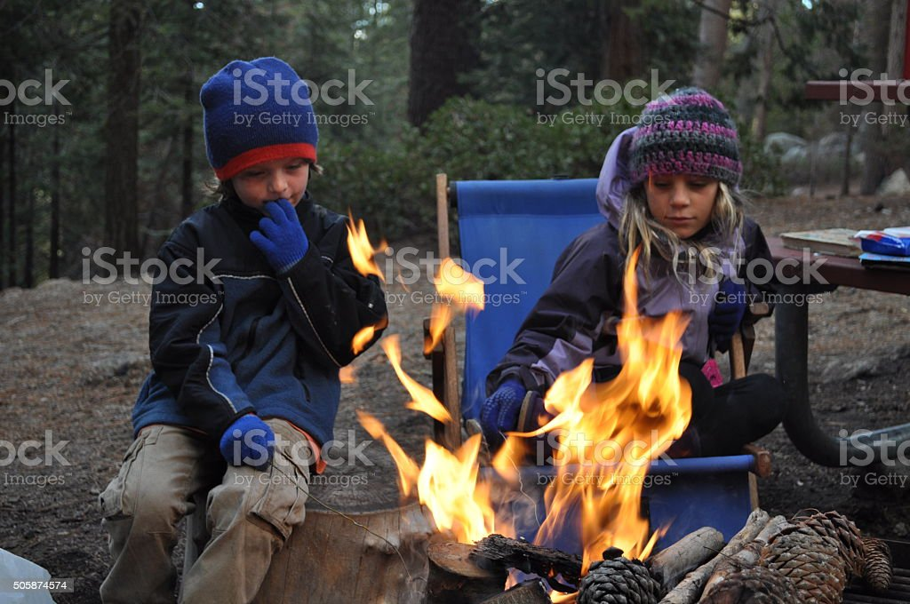 Kids sitting around a campfire stock photo