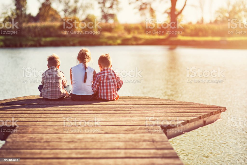 Kids sitting at the pier. stock photo
