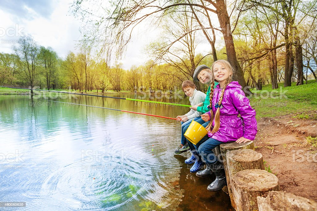 Kids sitting near pond holding fishing tackles stock photo