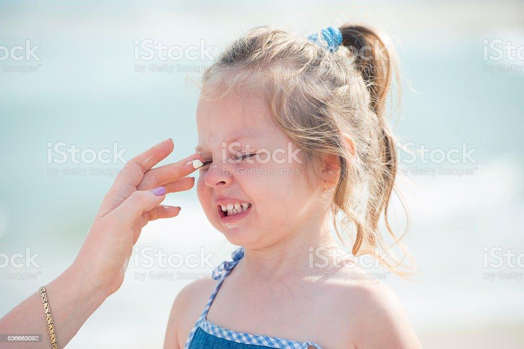 Kid's skin care at summer vacation. stock photo