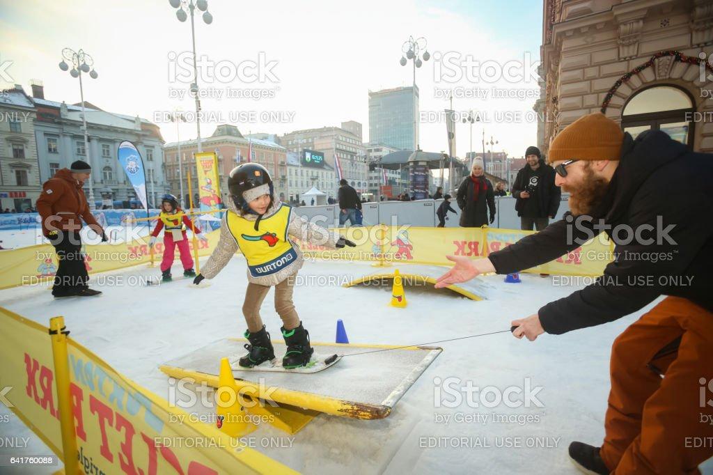 Kids snowboarding in city stock photo