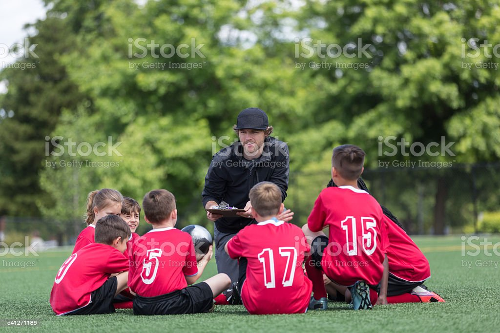 Kids soccer team listenting intently to their coach stock photo