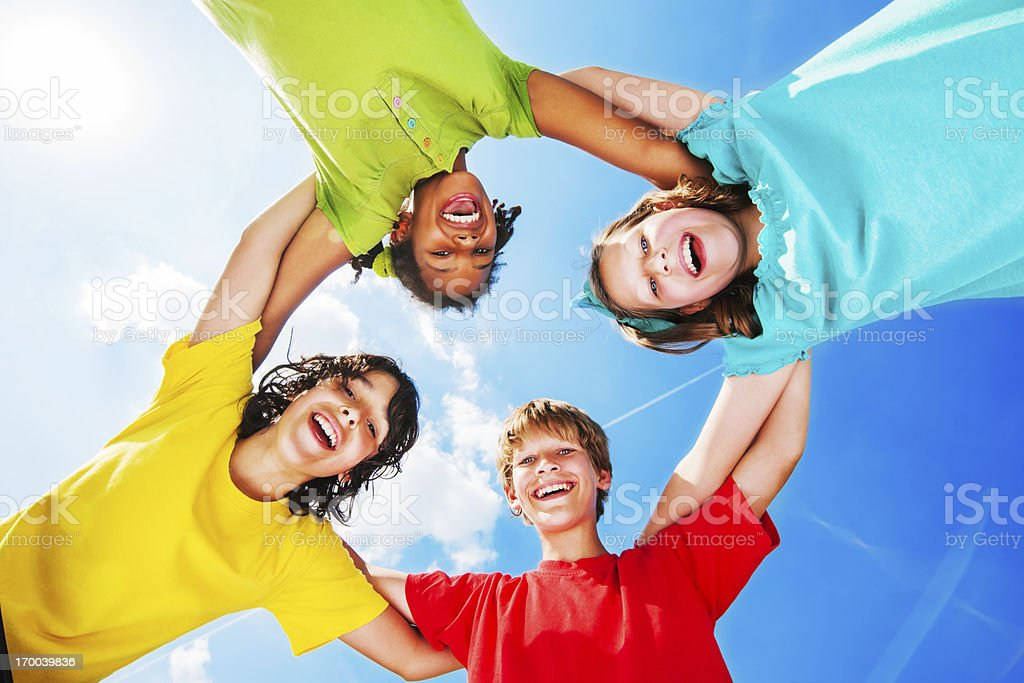 Kids standing embraced against the sky and clouds royalty-free stock photo