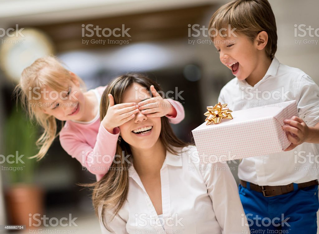 Kids surprising mom on mother's day stock photo