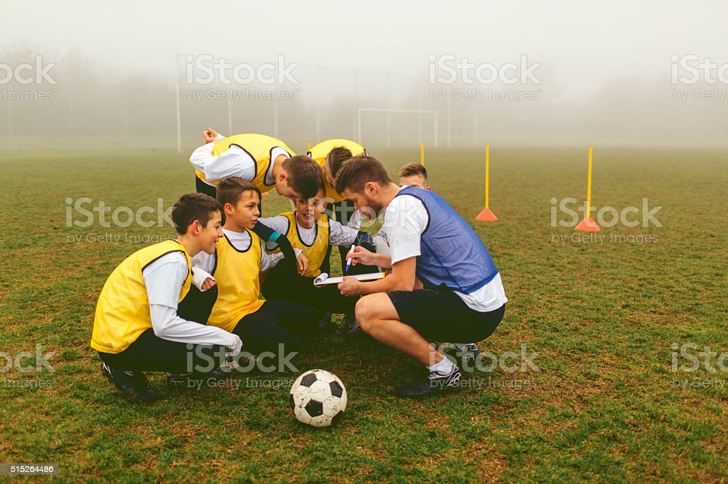 Kids Talking With Coach About Soccer Strategy stock photo