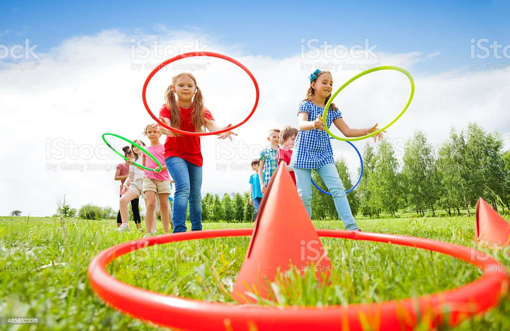 Kids throw colorful hoops on cones while competing stock photo