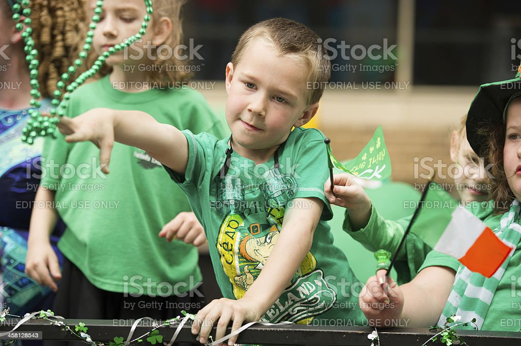Kids throwing beads to St. Patrick's Day Parade goers stock photo
