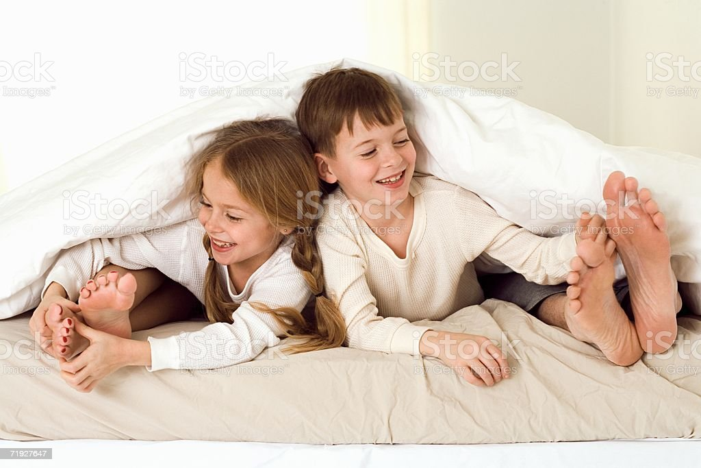 Kids tickling parents' feet stock photo