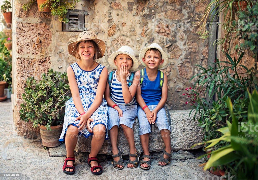 Kids tourist resting in mediterranean street. stock photo