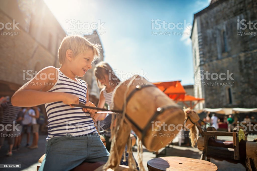 Kids tourists having fun on carousel in Volterra, Tuscany stock photo