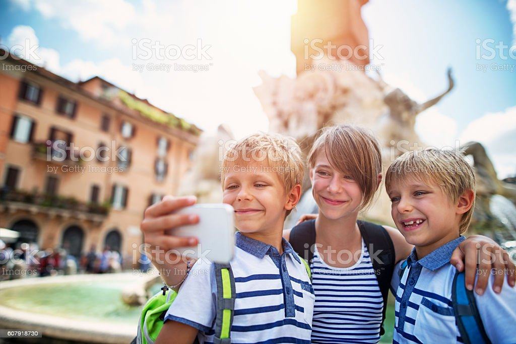 Kids tourists making selfie at Fontana dei Fiumi, Rome stock photo