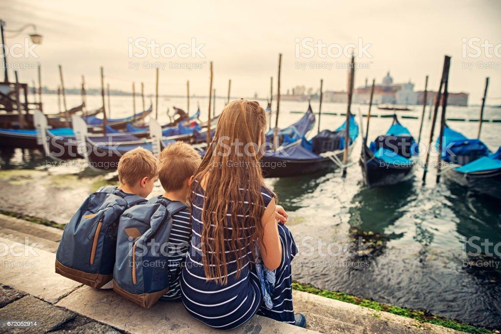 Kids tourists resting near gondola moorings in Venice, Italy stock photo