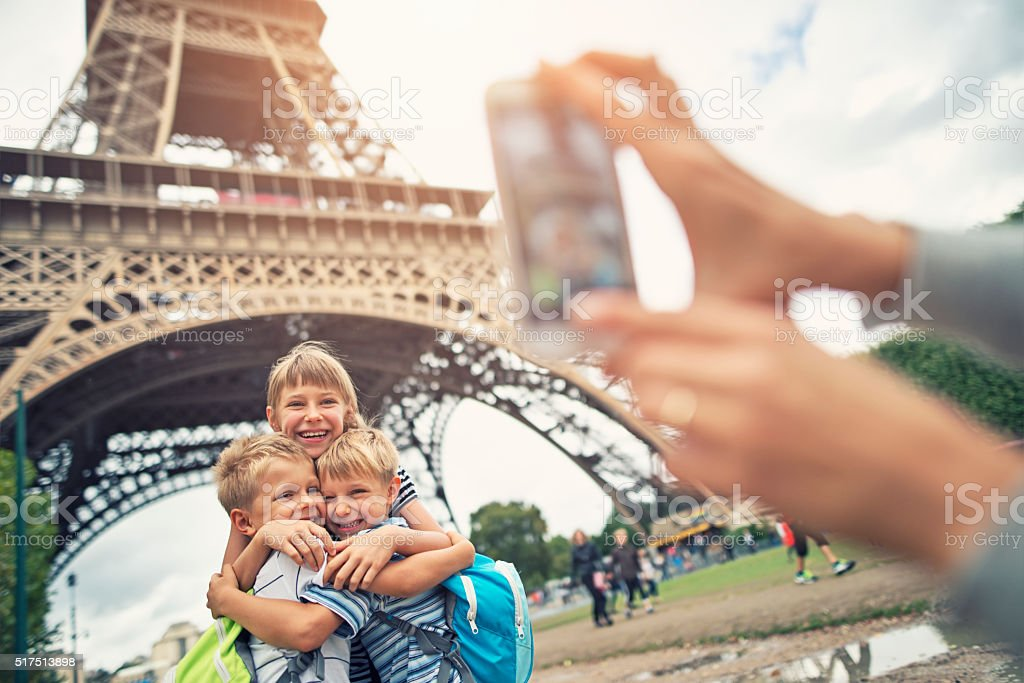 Kids tourists smiling at the camera near Eiffel Tower stock photo