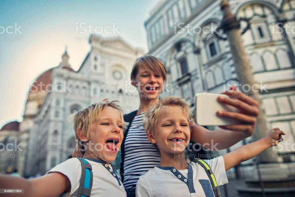 Kids tourists taking selfie in Florence, near the cathedral stock photo