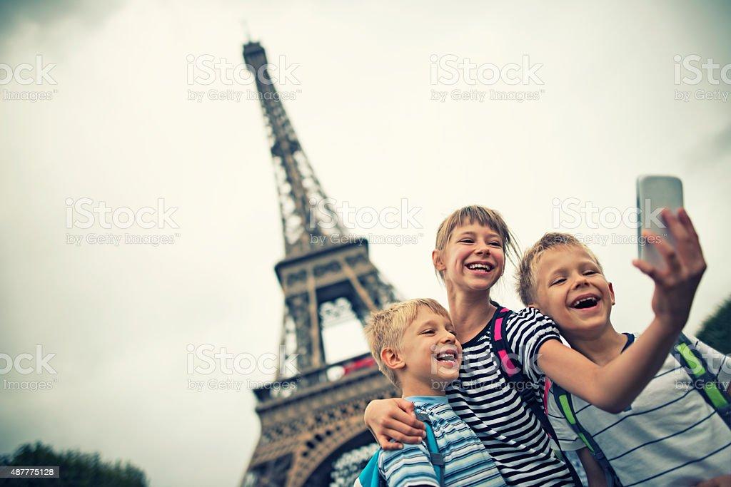 Kids tourists taking selfie near Eiffel Tower stock photo