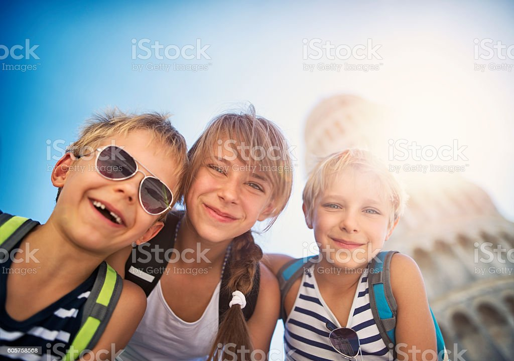 Kids tourists taking selfies by the Leaning Tower of Pisa stock photo