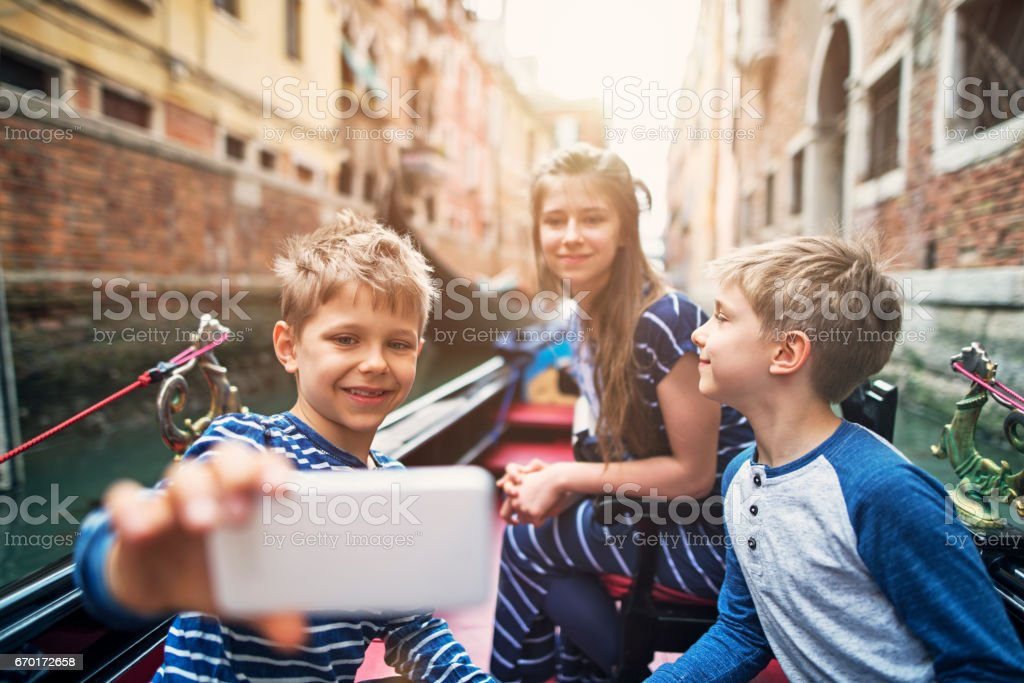 Kids tourists talking selfie during gondola ride in Venice, Italy stock photo
