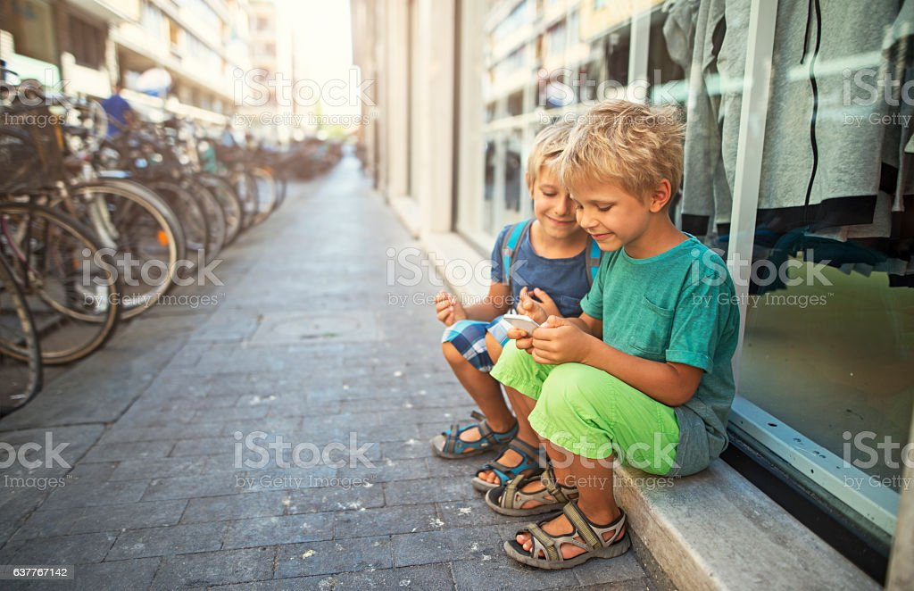 Kids tourists using smartphone in a street of Pisa, Italy stock photo