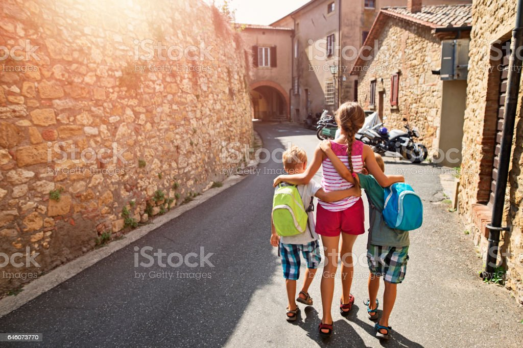 Kids tourists walking in street of italian town in Tuscany stock photo