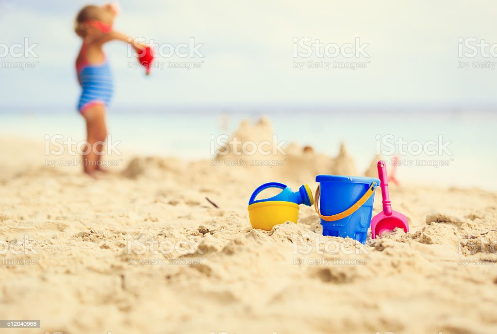 kids toys and little girl building sandcastle stock photo