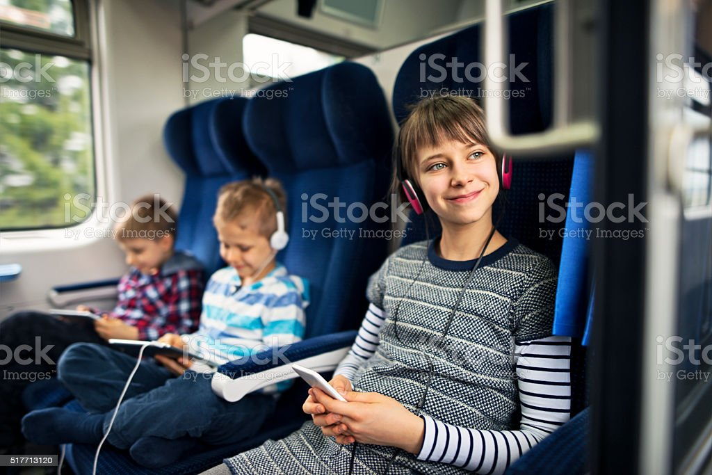 Kids travelling on train playing tablets and listening to music stock photo