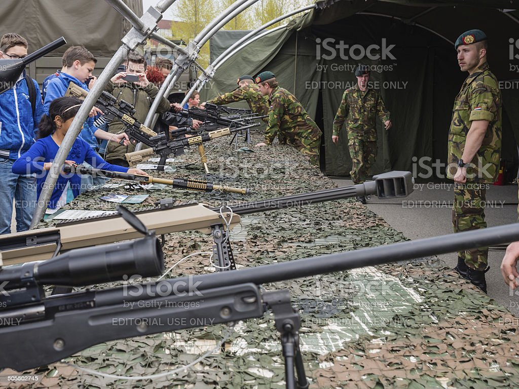 Kids trying rifles on army day stock photo