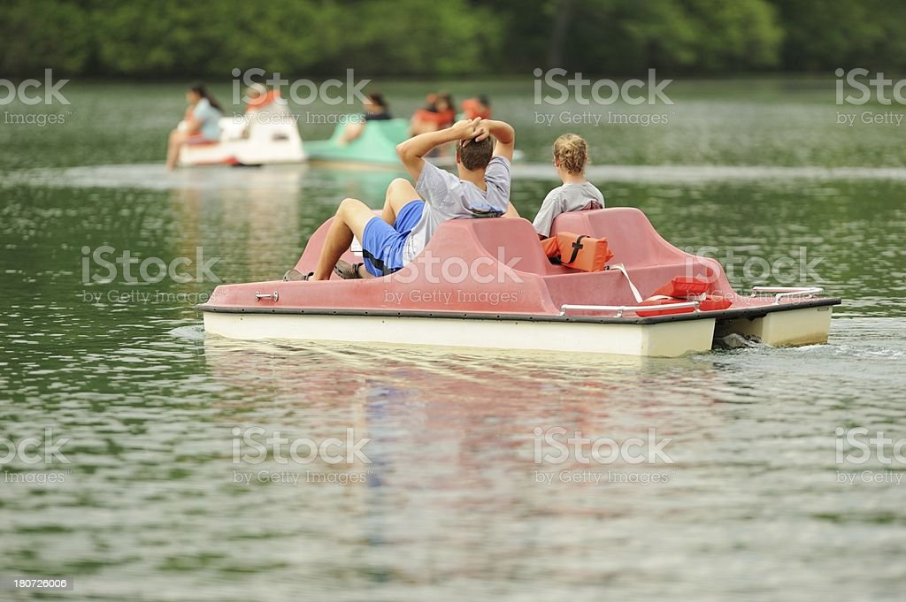 Kids using pedal boat on lake stock photo